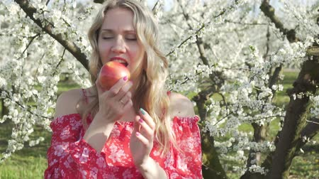 élvezet : Young woman eating an apple on the background of blooming apple trees.