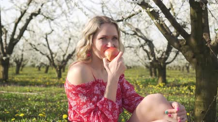 цветущий : Spring, young woman eating an apple on nature.