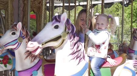 lő : A small child rides a horse carousel.