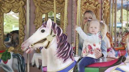 lő : A woman and a child riding a horse on a carousel. Stock mozgókép
