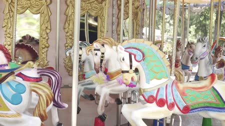 回転木馬 : Horses on the carousel ride in a circle, slow motion. Attraction, amusement Park.