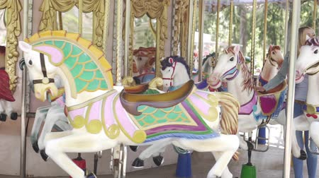 lő : Family rides on the carousel on horseback, amusement Park.
