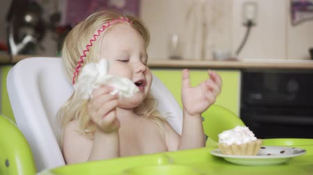 alimentacion bebe : Little baby girl eating at the childrens table. Archivo de Video