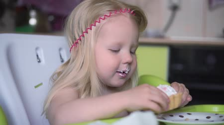 alimentacion bebe : Little child girl eating a cupcake in the kitchen, slow motion.