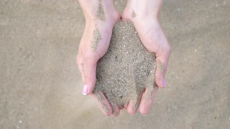 tırnak : Woman on a sandy beach. In her open palms sand pouring through her fingers.