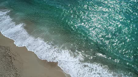 crete : Beautiful turquoise sea, waves and sandy beach, aerial view. Slow motion.