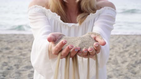 tırnak : A woman holds sand in her palms, sand pours through her fingers.
