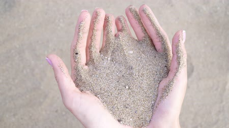 tırnak : Sand in female palms pour through fingers, close-up. Stok Video