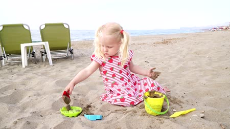 secchio : Girl child playing on a sandy beach with a scoop and bucket.