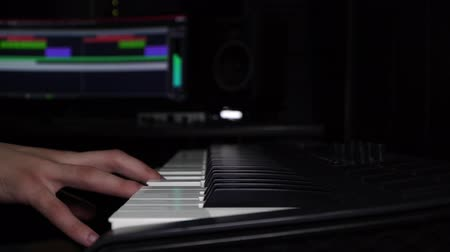 akord : A man plays the synthesizer, hand close-up. Recording studio, composer.