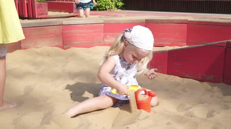plac zabaw : Girl child playing in the sandbox. A small child plays in the summer in the sandbox.