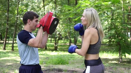kop : Young woman is engaged in boxing. A woman is boxing with a trainer.