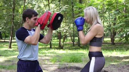 puncs : Young beautiful woman is practicing boxing. Woman boxing with an instructor. Stock mozgókép