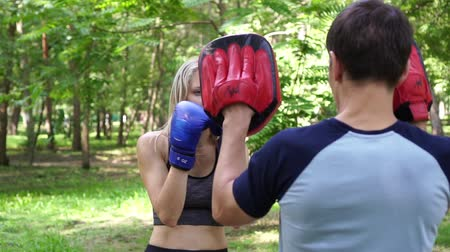 bokser : A woman is boxing with a trainer. Beautiful woman is engaged in boxing in the park.