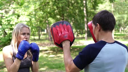 kop : Young beautiful woman is boxing in the park. Boxing training, womens self-defense. Dostupné videozáznamy