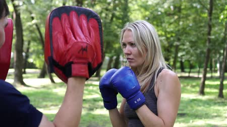 bokser : Beautiful woman boxing with a trainer. Portrait of a female boxer.