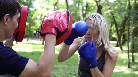 kop : Young woman is engaged in boxing with a trainer. Boxing training, slow motion.