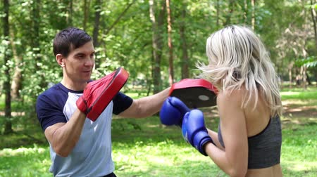 bokser : A woman with a coach is learning boxing, slow motion. Woman boxing in the park.