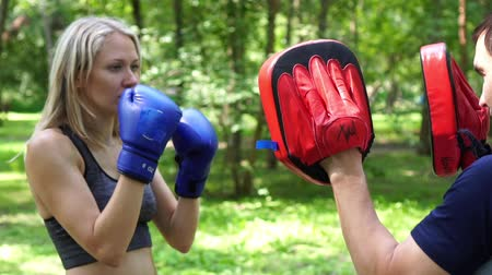 bokser : A woman is boxing with a trainer. Boxing training, modern woman.