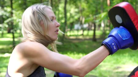 puncs : Portrait of a female boxer. Woman boxing, playing sports in nature.