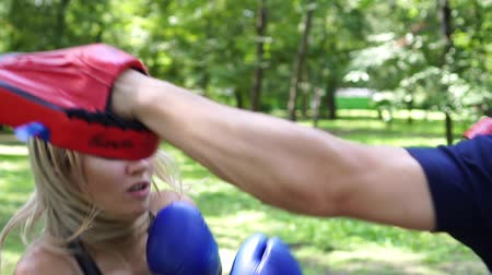 puncs : Woman boxing, slow motion. A woman is boxing with a trainer. Stock mozgókép