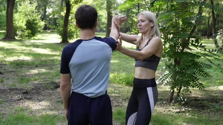 combate : A beautiful woman is studying martial arts and fighting techniques with a coach. Vídeos