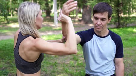 combate : Beautiful woman goes in for sports in the park with a trainer.
