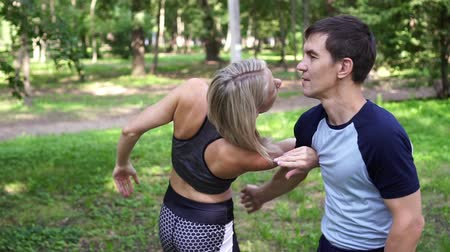 戦闘 : Woman trains in the park. Fight, self-defense, oriental martial arts.