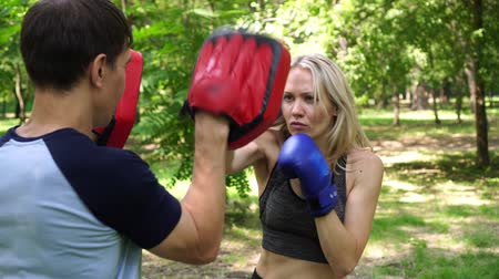 kop : Young woman is engaged in boxing in the park.
