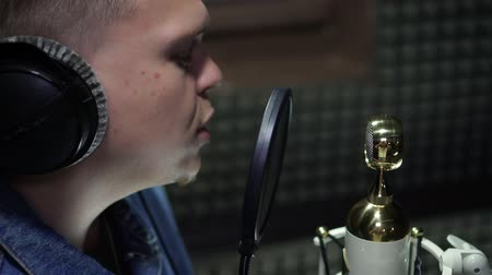 hang : A male singer reads rap, records a song in a recording studio. Stock mozgókép