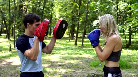 bokser : A woman is boxing in a park with a trainer.