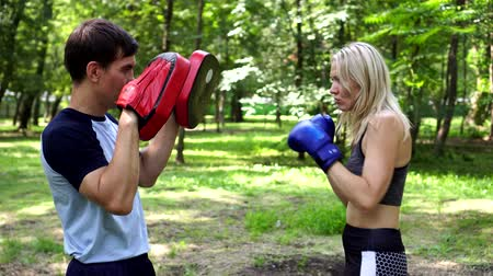 bokser : Beautiful woman is boxing in the park with a trainer.