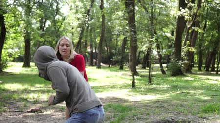 włamywacz : A woman defends herself against a criminal in a park. Womens self-defense.