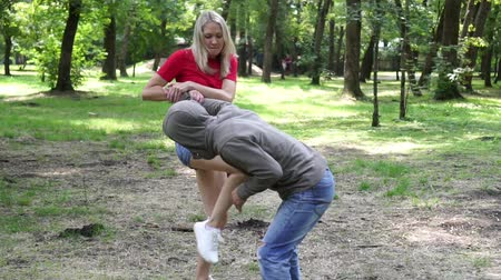 хулиган : A woman fights with a criminal a bully in the park. Стоковые видеозаписи
