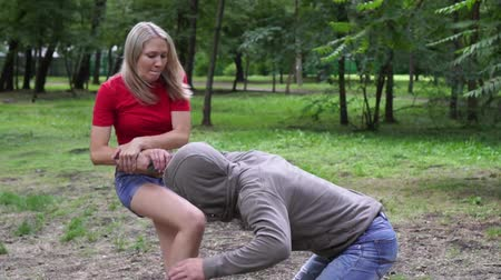 włamywacz : Womens self-defense. A woman fights with a criminal a bully in the park.