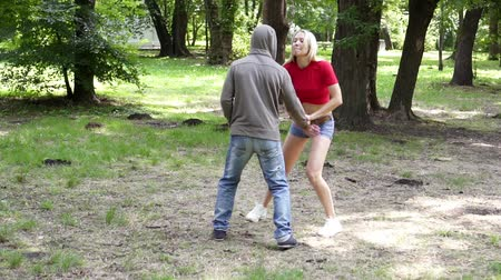 włamywacz : A man attacks a woman in a park, a fight, female self-defense.