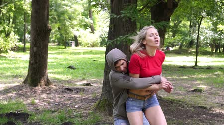 włamywacz : A male bully attacks a woman in a park. Womens self-defense.