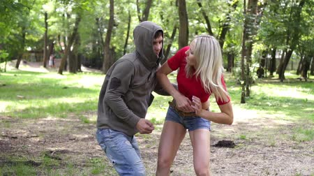 włamywacz : A woman is fighting a man with a criminal who attacked her in a park.