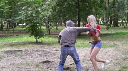 włamywacz : A woman is fighting a man with a criminal who attacked her in a park. Womens self-defense.