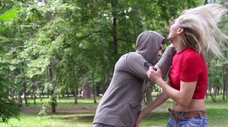 tehdit : Female self-defense training in the park. A woman is practicing hand-to-hand combat.