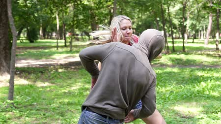 włamywacz : A woman is practicing hand-to-hand combat. Female self-defense training in the park. Wideo