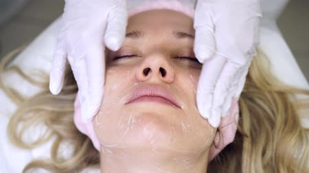 уборка : Portrait of a woman in a beauty salon at the beautician. Skin care, rejuvenation. Стоковые видеозаписи