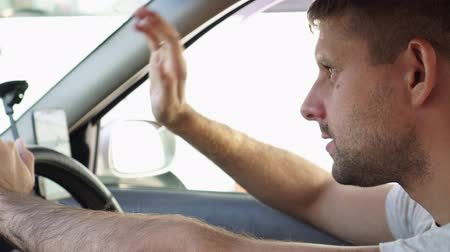 джем : A male driver is angry in a traffic jam driving a car.