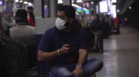 tosse : Agra, India, - March 2020. Asian male in medical mask at the railway station. Stock Footage