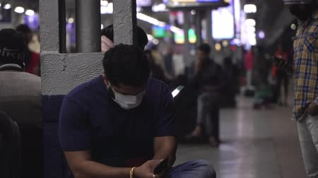 tosse : Agra, India, - March 2020. A man in a medical mask at a train station waiting for a train.