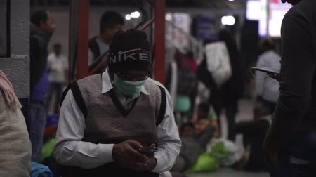 tosse : Agra, India, - March 2020. Male passenger in a medical mask at the station with a smartphone. Stock Footage