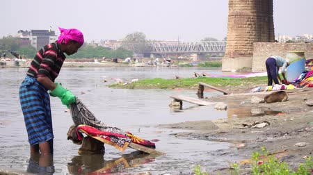 lavanderia : Agra, India, - March 2020. Indian worker washing clothes on the river.