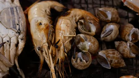 seafood dishes : Grilled Shrimp, shellfish and crab on stove grille , cooking barbecue seafood.