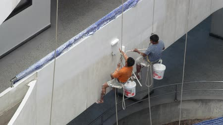 harness : Bangkok, Thailand - December,4 2018 : Painters are painting on high buildings with the big rope. Stock Footage