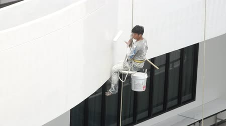 work at height : Bangkok, Thailand - December,4 2018 : Painters are painting on high buildings with the big rope. Stock Footage